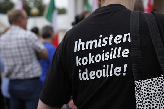 T-paidan selkä, jossa lukee Ihmisten kokoisille ideoille
