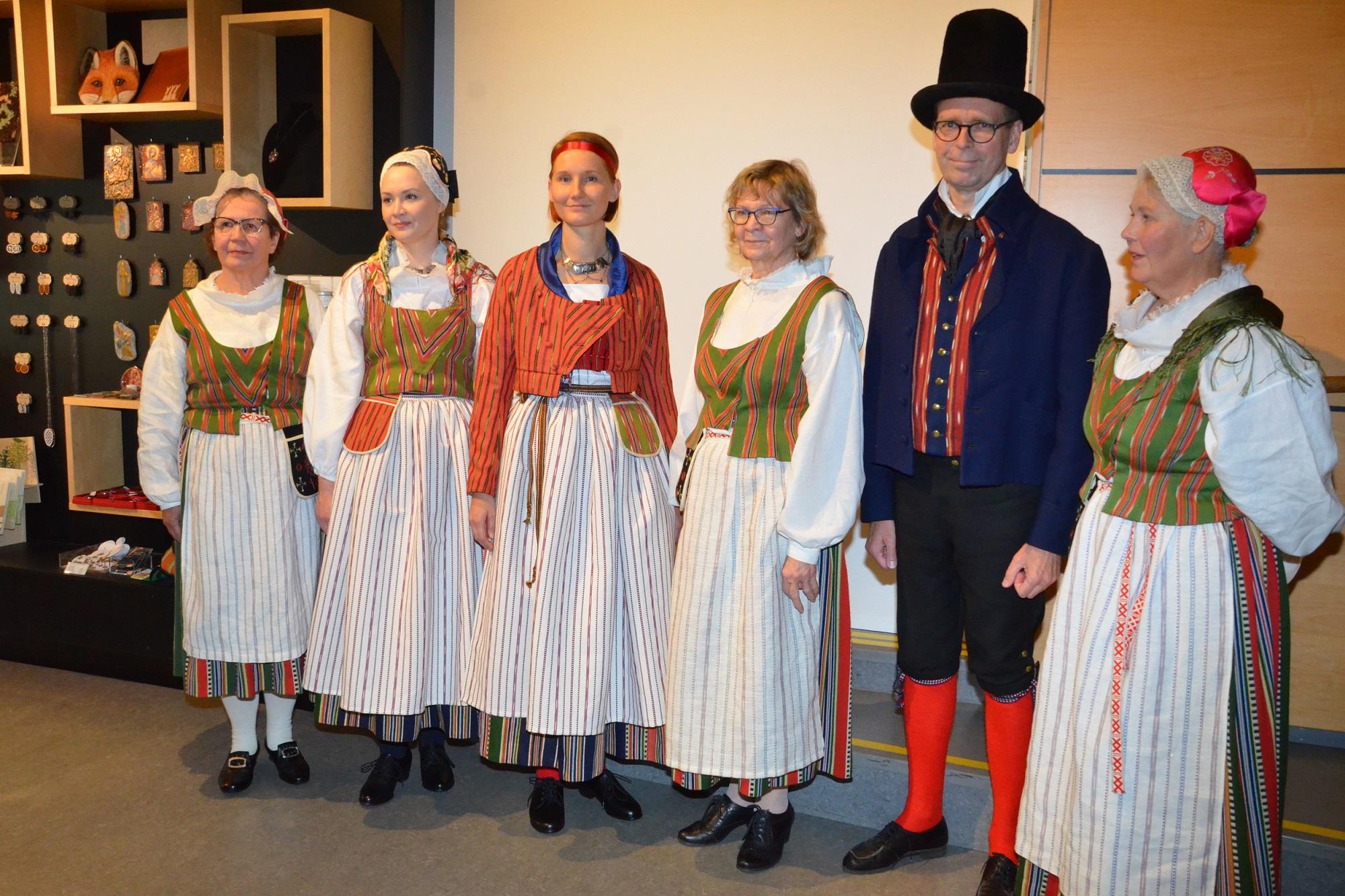 Ikaalisten kansallispukuja rivissä viisi naisen pukua ja yksi miehn puku