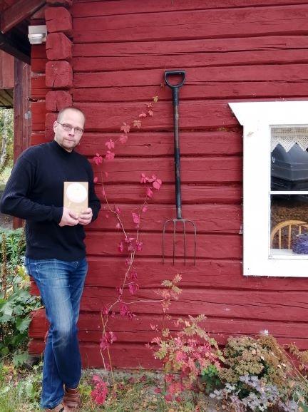 Roope Lipasti nojaa punaiseen taloon, jonka seinässä heinähanko