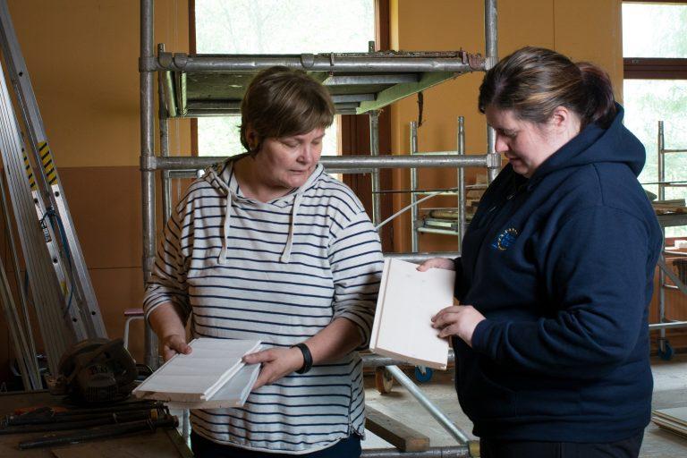 Kaksi naista tutkii värinäytteitä rakennustyömaalla