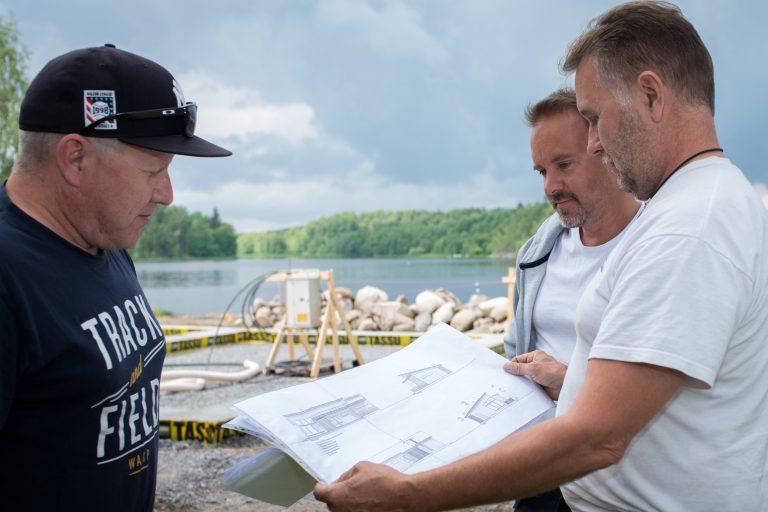 Kolme miestä tutkii piirustuksia