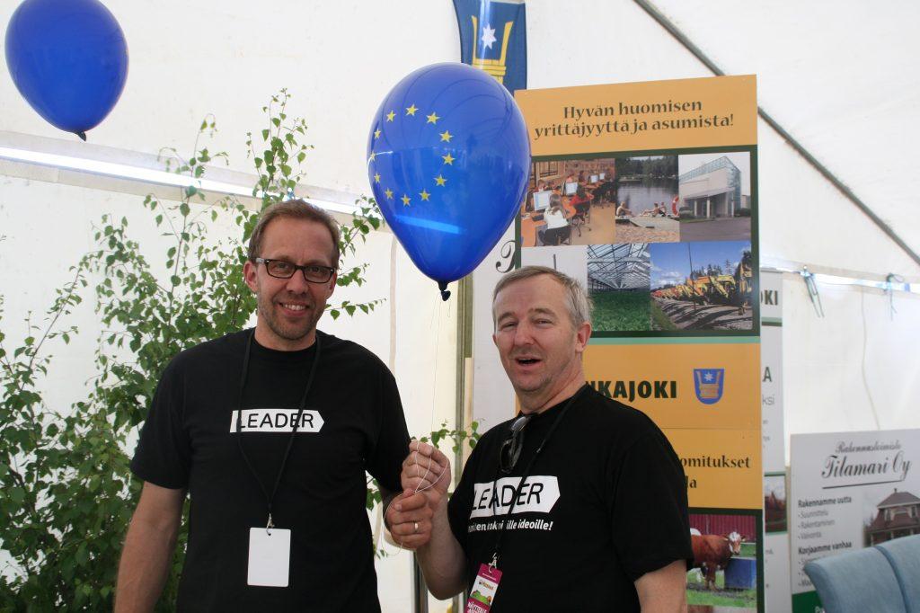 Juha ja Paavo Honkajoella Masiinamessuilla seisovat ständin edessä