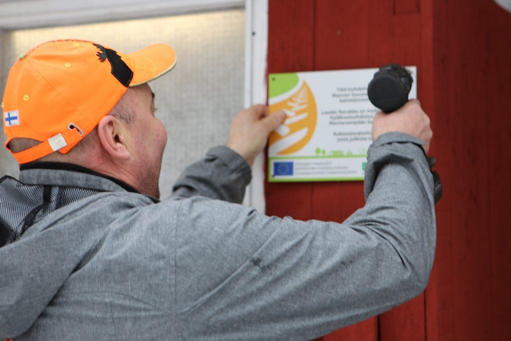 Mies kiinnittää maaseuturahoituksen kylttiä.