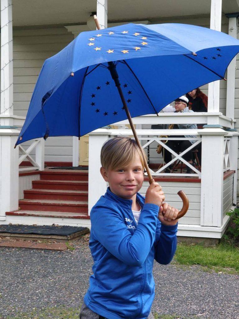 poika sateenvarjon kanssa