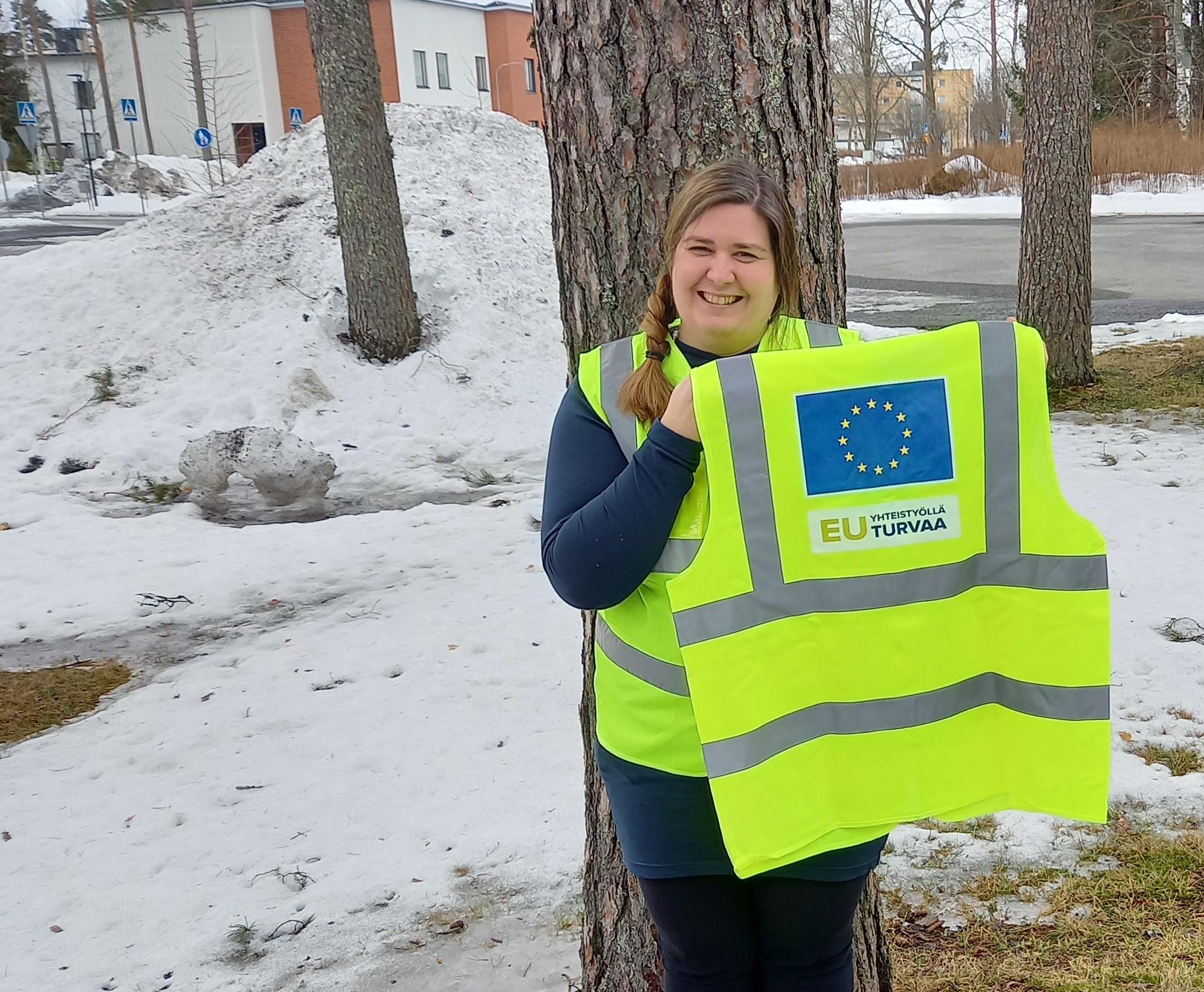 Nainen esittelee turvaliiviä, jossa EU lipuu ja teksti EU turvaa