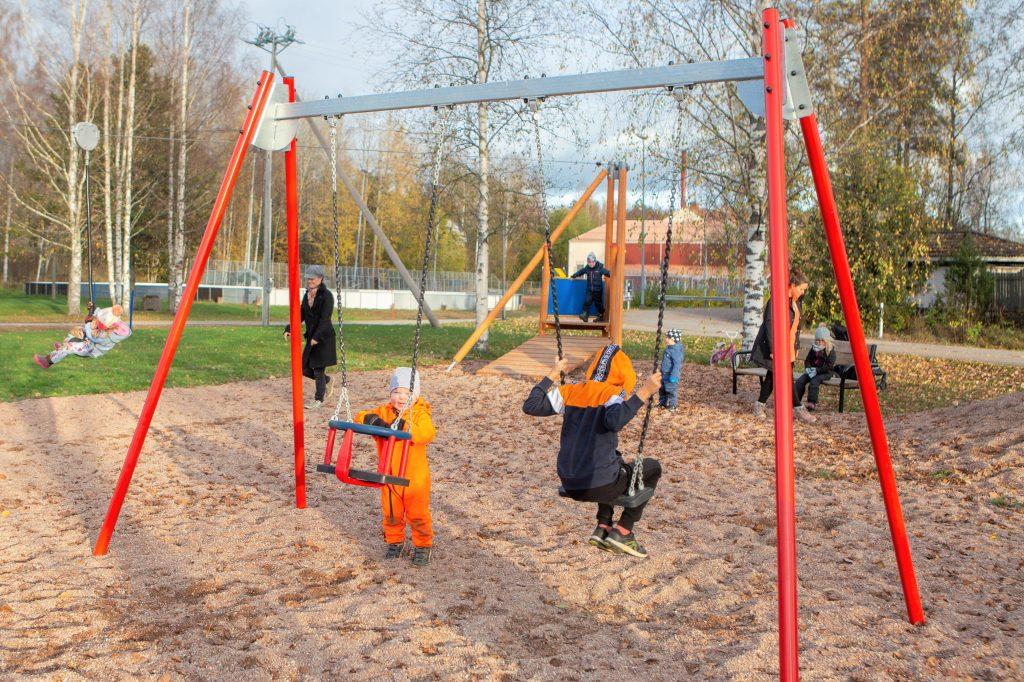 lapsia keinumassa leikkipuistossa