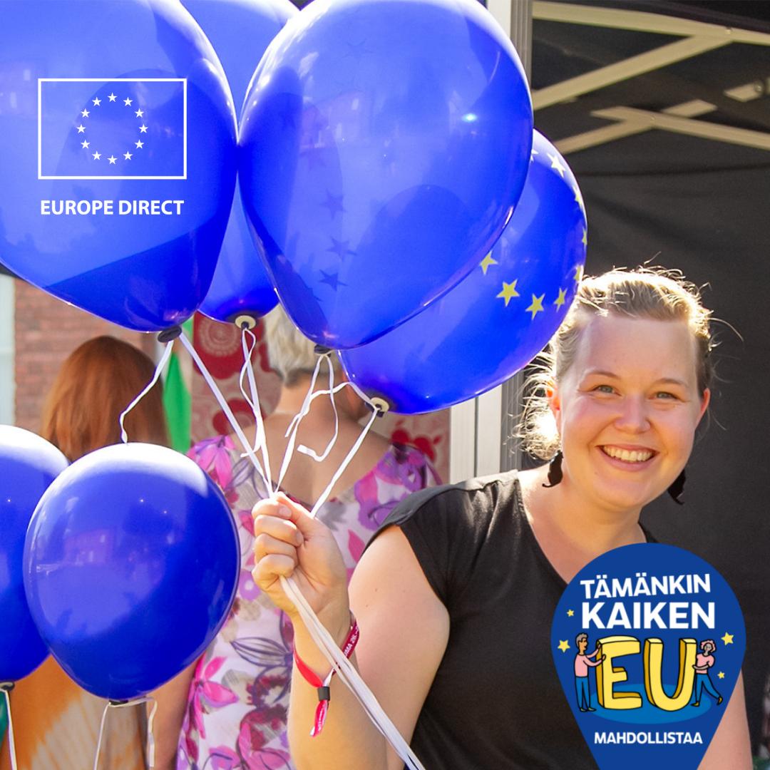 Nainen pitää käsissään EU-ilmapalloja ja hymyilee