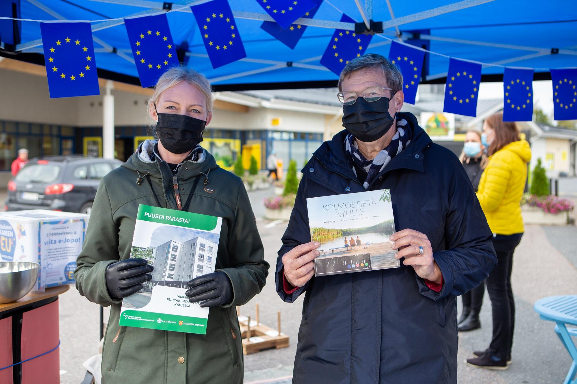 Kaksi naista pitää eisttelitä kädessään ja katsoo kameraan EU lippujen all,a kuvituskuva