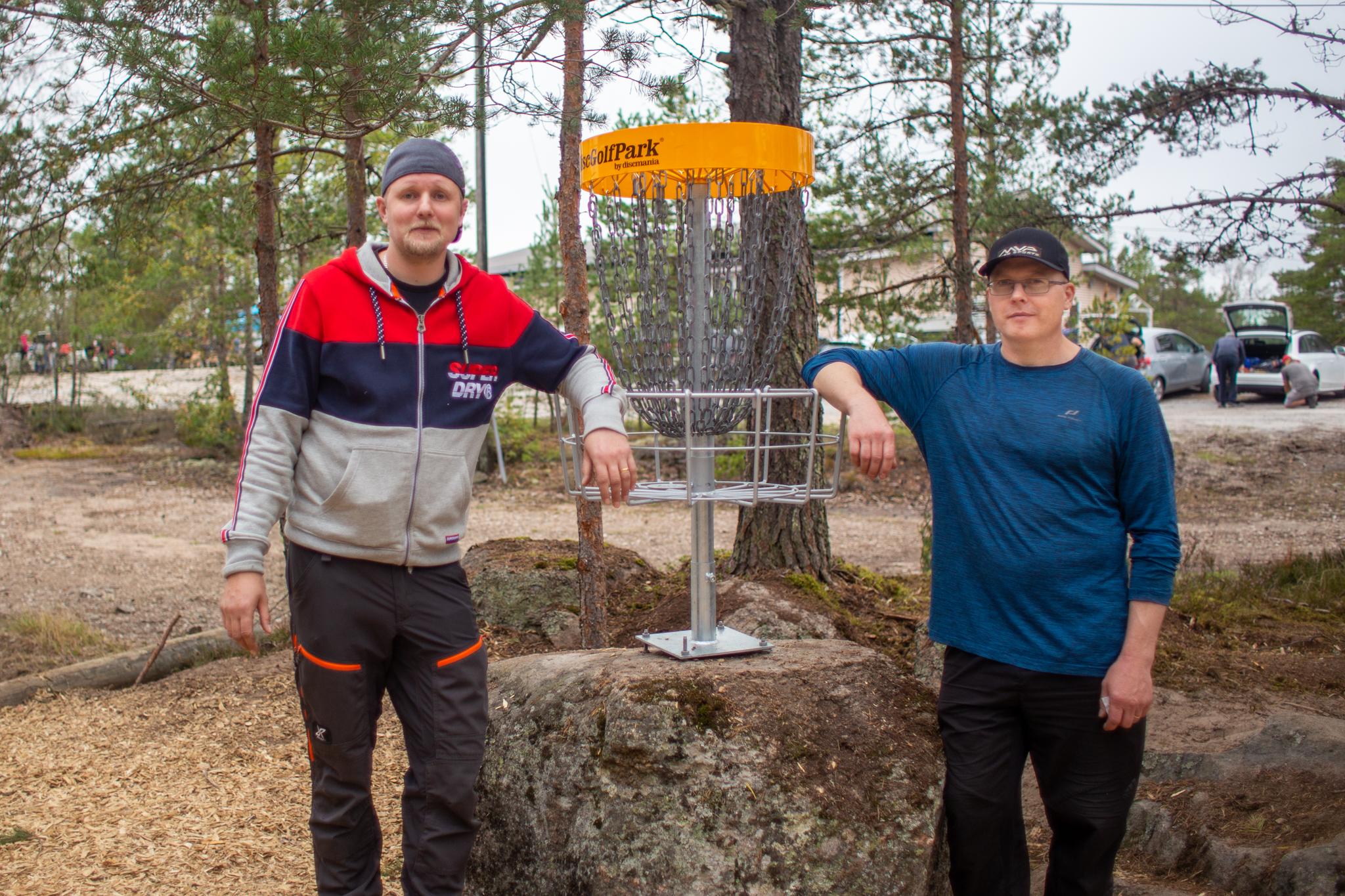 Ville Aerila ja Pekka Siivonen Kirikallion frisbeegolfradalla nojaamassa koriin.